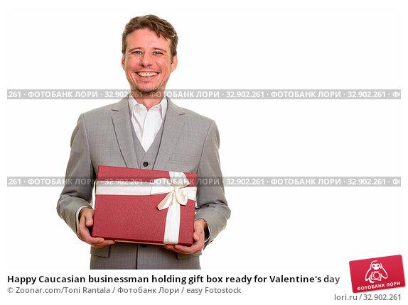 Happy Caucasian businessman holding gift box ready for Valentine's day. Стоковое фото, фотограф Zoonar.com/Toni Rantala / easy Fotostock / Фотобанк Лори