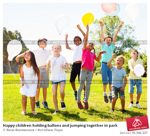 Happy children holding ballons and jumping together in park. Стоковое фото, фотограф Яков Филимонов / Фотобанк Лори