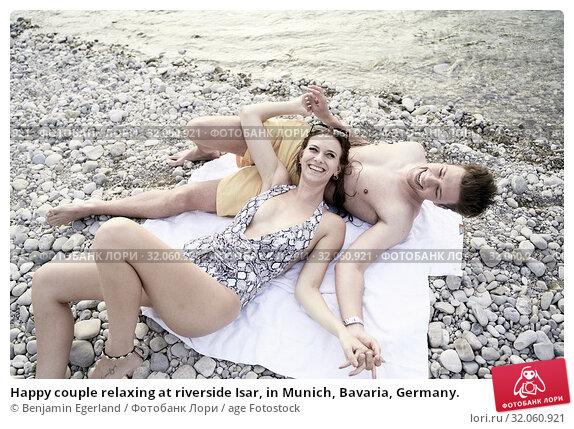 Happy couple relaxing at riverside Isar, in Munich, Bavaria, Germany. Стоковое фото, фотограф Benjamin Egerland / age Fotostock / Фотобанк Лори