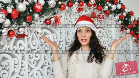 Купить «Happy excited young woman wearing santa red hat is looking at the camera with surprise in studio on Christmas decorated background», видеоролик № 29799225, снято 3 декабря 2018 г. (c) Ольга Балынская / Фотобанк Лори