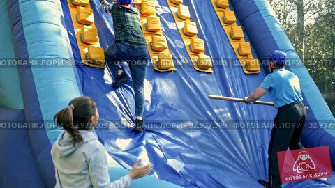 Happy friends enjoying a day at amusement park, climbing on inflatable slide with wooden poles. Стоковое видео, видеограф Яков Филимонов / Фотобанк Лори