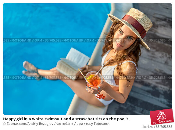 Happy girl in a white swimsuit and a straw hat sits on the pool's... Стоковое фото, фотограф Zoonar.com/Andriy Bezuglov / easy Fotostock / Фотобанк Лори