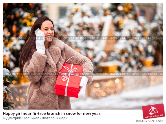 Happy girl near fir-tree branch in snow for new year. Стоковое фото, фотограф Дмитрий Травников / Фотобанк Лори