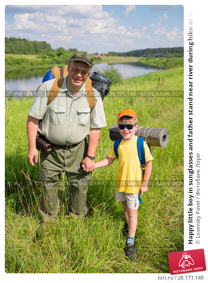 Купить «Happy little boy in sunglasses and father stand near river during hike at summer day», фото № 28171149, снято 3 июля 2016 г. (c) Losevsky Pavel / Фотобанк Лори