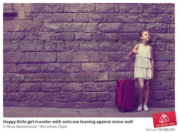 Купить «Happy little girl traveler with suitcase leaning against stone wall», фото № 28808081, снято 17 августа 2017 г. (c) Яков Филимонов / Фотобанк Лори