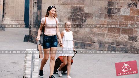 Купить «Happy mother with daughter walking with luggage on European city during summer vacation», видеоролик № 27237277, снято 23 августа 2017 г. (c) Яков Филимонов / Фотобанк Лори