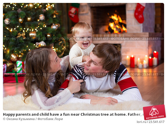 Купить «Happy parents and child have a fun near Christmas tree at home. Father, mother, son celebrating New Year together», фото № 23541617, снято 7 декабря 2015 г. (c) Оксана Кузьмина / Фотобанк Лори