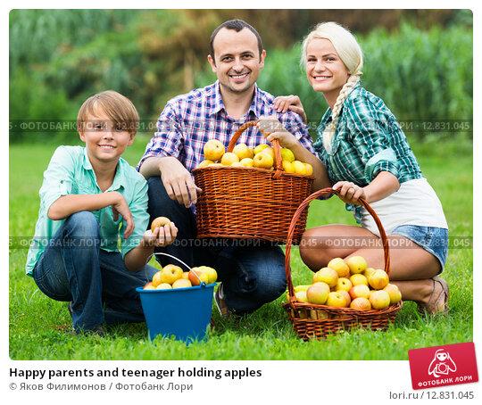 Купить «Happy parents and teenager holding apples», фото № 12831045, снято 24 апреля 2019 г. (c) Яков Филимонов / Фотобанк Лори
