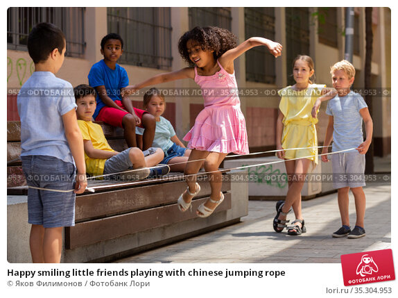 Happy smiling little friends playing with chinese jumping rope. Стоковое фото, фотограф Яков Филимонов / Фотобанк Лори