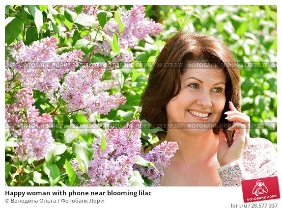Купить «Happy woman with phone near blooming lilac», фото № 28577337, снято 16 мая 2018 г. (c) Володина Ольга / Фотобанк Лори