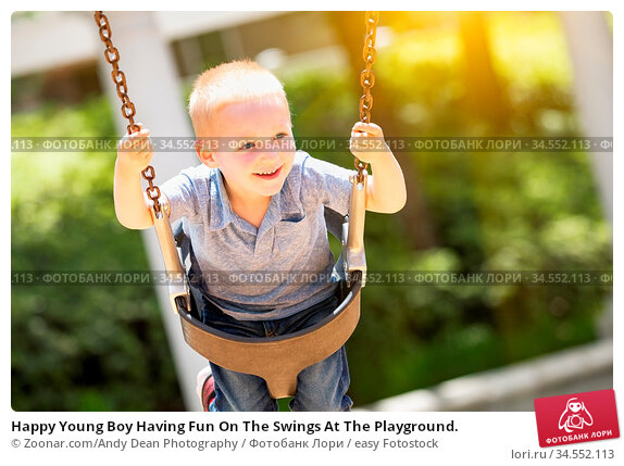 Happy Young Boy Having Fun On The Swings At The Playground. Стоковое фото, фотограф Zoonar.com/Andy Dean Photography / easy Fotostock / Фотобанк Лори