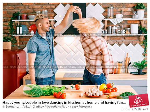 Happy young couple in love dancing in kitchen at home and having fun... Стоковое фото, фотограф Zoonar.com/Viktor Gladkov / easy Fotostock / Фотобанк Лори