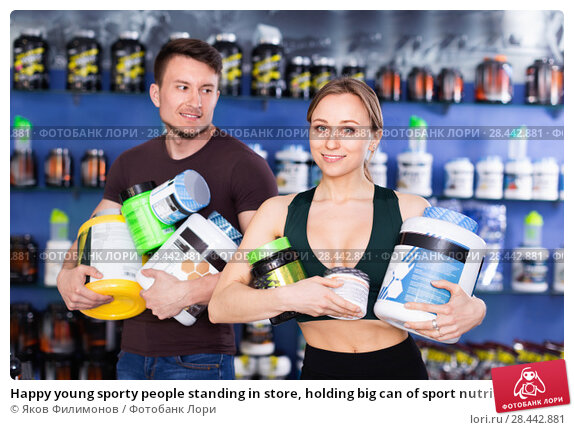 Купить «Happy young sporty people standing in store, holding big can of sport nutrition», фото № 28442881, снято 12 апреля 2018 г. (c) Яков Филимонов / Фотобанк Лори