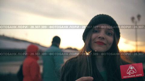 Купить «Happy young woman with sparkler at sunset outdoors», видеоролик № 28307389, снято 20 апреля 2018 г. (c) Константин Шишкин / Фотобанк Лори