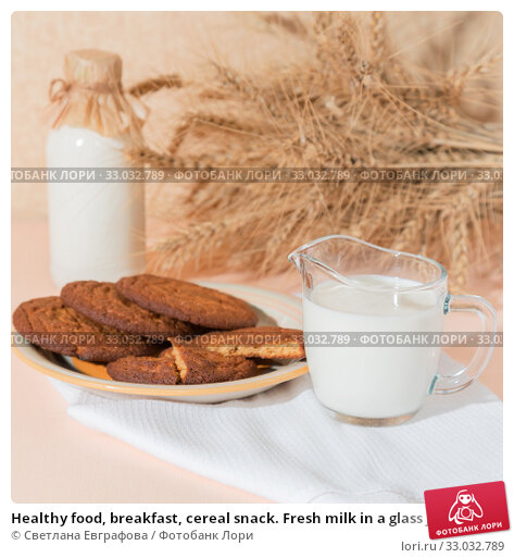 Купить «Healthy food, breakfast, cereal snack. Fresh milk in a glass jug and oatmeal cookies on the table, an armful of ears of corn on a peach color background. A balanced diet, protein and carbohydrates», фото № 33032789, снято 30 ноября 2019 г. (c) Светлана Евграфова / Фотобанк Лори