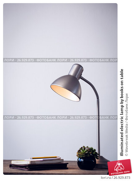 Купить «Illuminated electric lamp by books on table», фото № 26929873, снято 26 мая 2017 г. (c) Wavebreak Media / Фотобанк Лори