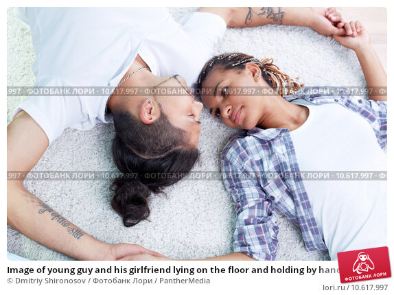 Image of young guy and his girlfriend lying on the floor and holding by hands. Стоковое фото, фотограф Dmitriy Shironosov / PantherMedia / Фотобанк Лори