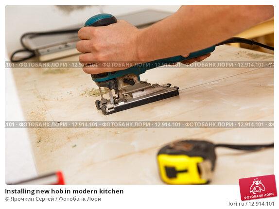 Купить «Installing new hob in modern kitchen», фото № 12914101, снято 2 сентября 2015 г. (c) Ярочкин Сергей / Фотобанк Лори
