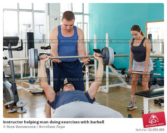 Instructor helping man doing exercises with barbell. Стоковое фото, фотограф Яков Филимонов / Фотобанк Лори