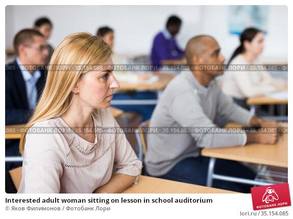 Interested adult woman sitting on lesson in school auditorium. Стоковое фото, фотограф Яков Филимонов / Фотобанк Лори