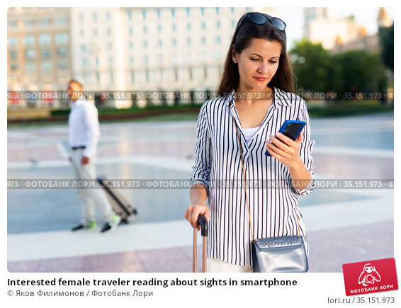 Interested female traveler reading about sights in smartphone. Стоковое фото, фотограф Яков Филимонов / Фотобанк Лори