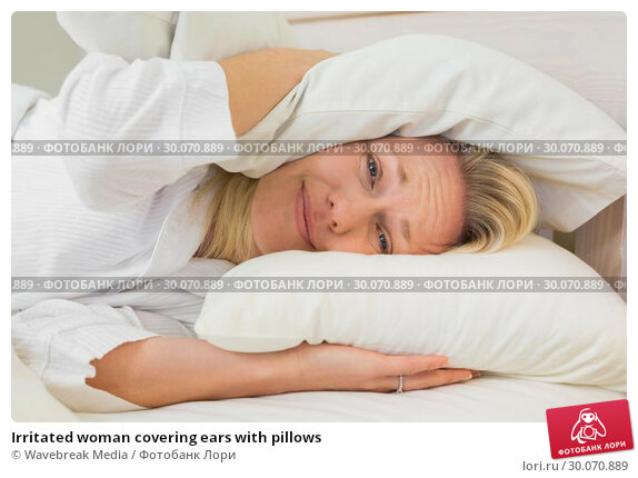 Купить «Irritated woman covering ears with pillows», фото № 30070889, снято 18 декабря 2013 г. (c) Wavebreak Media / Фотобанк Лори