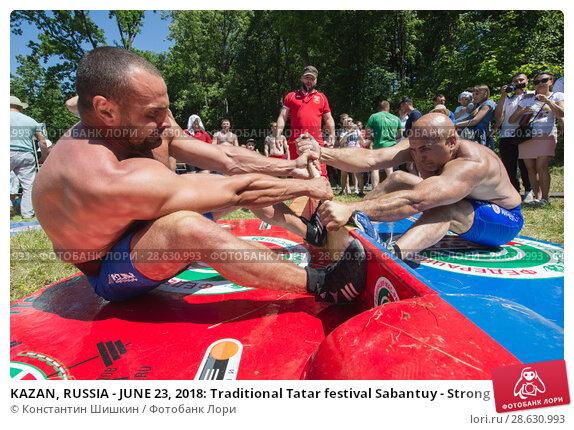 Купить «KAZAN, RUSSIA - JUNE 23, 2018: Traditional Tatar festival Sabantuy - Strong men wrestling outdoors at summer day», фото № 28630993, снято 23 июня 2018 г. (c) Константин Шишкин / Фотобанк Лори