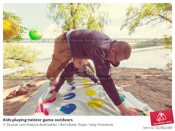 Kids playing twister game outdoors. Стоковое фото, фотограф Zoonar.com/Galyna Andrushko / easy Fotostock / Фотобанк Лори