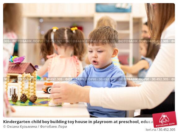 Kindergarten child boy building toy house in playroom at preschool, education concept. Стоковое фото, фотограф Оксана Кузьмина / Фотобанк Лори