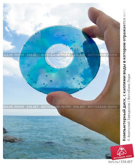 Компьютерный диск, с каплями воды в котором отражается небо в руке, на фоне моря, фото № 318457, снято 27 мая 2006 г. (c) Анатолий Заводсков / Фотобанк Лори