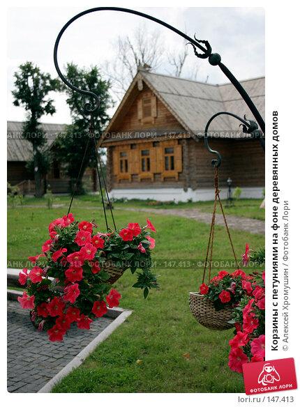 Корзины с петуниями на фоне деревянных домов, фото № 147413, снято 14 июля 2007 г. (c) Алексей Хромушин / Фотобанк Лори