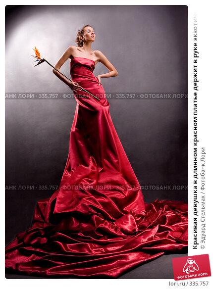 Красивая девушка в длинном красном платье держит в руке экзотический цветок, фото № 335757, снято 25 декабря 2007 г. (c) Эдуард Стельмах / Фотобанк Лори