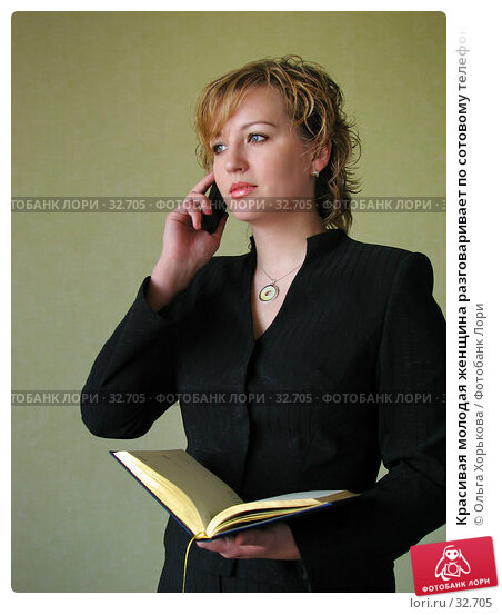 Красивая молодая женщина разговаривает по сотовому телефону и держит в руках раскрытую книгу, фото № 32705, снято 12 апреля 2007 г. (c) Ольга Хорькова / Фотобанк Лори