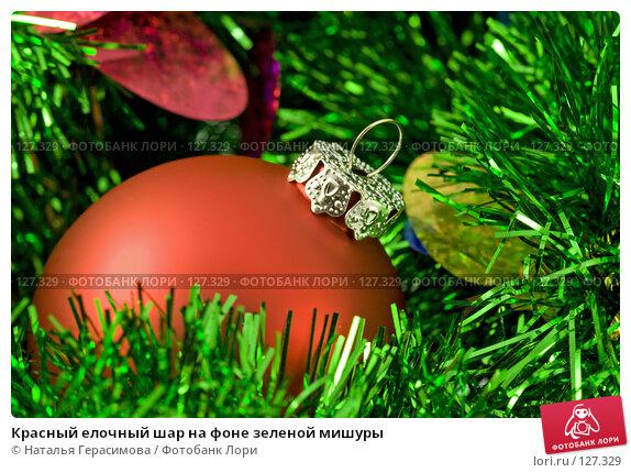 Красный елочный шар на фоне зеленой мишуры, фото № 127329, снято 20 июля 2017 г. (c) Наталья Герасимова / Фотобанк Лори