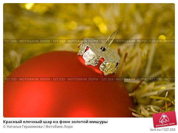 Купить «Красный елочный шар на фоне золотой мишуры», фото № 127333, снято 6 ноября 2007 г. (c) Наталья Герасимова / Фотобанк Лори