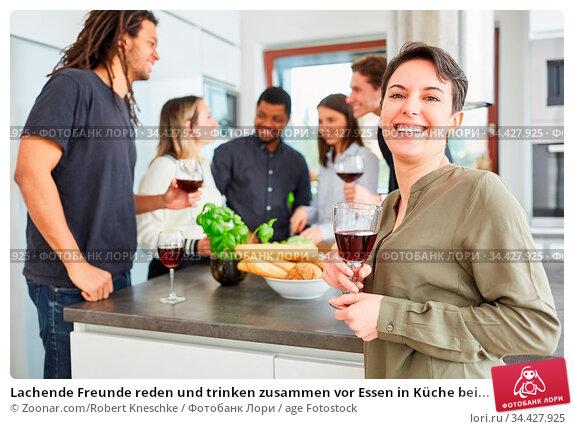Lachende Freunde reden und trinken zusammen vor Essen in Küche bei... Стоковое фото, фотограф Zoonar.com/Robert Kneschke / age Fotostock / Фотобанк Лори