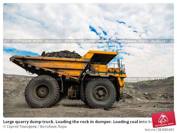 Купить «Large quarry dump truck. Loading the rock in dumper. Loading coal into body truck. Production useful minerals. Mining truck mining machinery, to transport coal from open-pit as the coal production.», фото № 28843661, снято 22 июня 2018 г. (c) Сергей Тимофеев / Фотобанк Лори