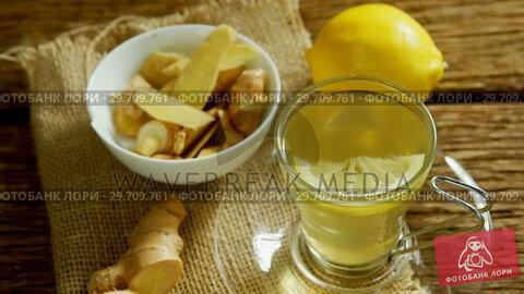 Купить «Lemon tea with ginger and lemon on wooden table 4k», видеоролик № 29709761, снято 12 июня 2017 г. (c) Wavebreak Media / Фотобанк Лори