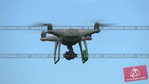 Летящий квадрокоптер Phantom 4 Pro на фоне голубого неба. Редакционное видео, видеограф Виктор Карасев / Фотобанк Лори