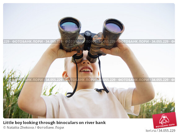 Купить «Little boy looking through binoculars on river bank», фото № 34055229, снято 6 июня 2015 г. (c) Nataliia Zhekova / Фотобанк Лори