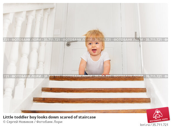Little toddler boy looks down scared of staircase. Стоковое фото, фотограф Сергей Новиков / Фотобанк Лори