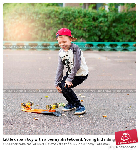 Little urban boy with a penny skateboard. Young kid riding in the... Стоковое фото, фотограф Zoonar.com/NATALIIA ZHEKOVA / easy Fotostock / Фотобанк Лори