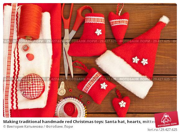 Купить «Making traditional handmade red Christmas toys: Santa hat, hearts, mittens and gift sock. Materials and accessories for needlework. New Year's still life», фото № 29427625, снято 10 декабря 2017 г. (c) Виктория Катьянова / Фотобанк Лори