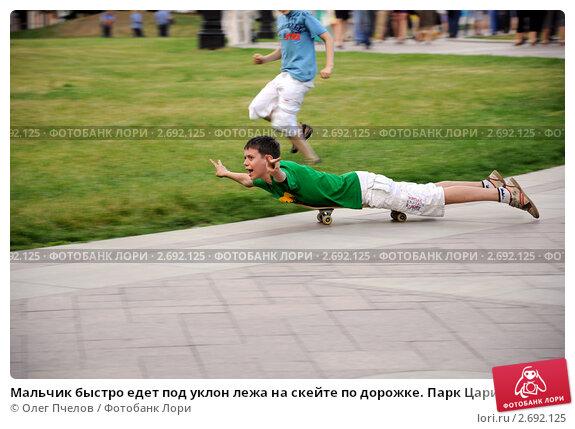 Мальчик быстро едет под уклон лежа на скейте по дорожке. Парк Царицыно. Москва. Редакционное фото, фотограф Олег Пчелов / Фотобанк Лори