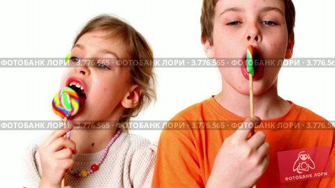 Мальчик и маленькая девочка с леденцами на палочке на белом фоне. Стоковое видео, видеограф Losevsky Pavel / Фотобанк Лори