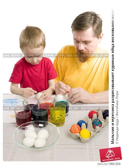 Купить «Мальчик и мужчина разрисовывают куриные яйца восковыми мелками», фото № 980509, снято 18 апреля 2009 г. (c) Надежда Щур / Фотобанк Лори