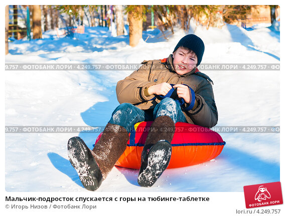 Купить «Мальчик-подросток спускается с горы на тюбинге-таблетке», эксклюзивное фото № 4249757, снято 26 января 2013 г. (c) Игорь Низов / Фотобанк Лори