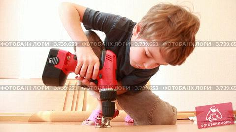 Купить «Мальчик соединяет детали мебели шуруповертом», видеоролик № 3739653, снято 5 июня 2011 г. (c) Losevsky Pavel / Фотобанк Лори
