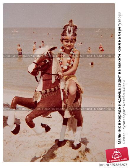 Купить «Мальчик в наряде индейца сидит на макете коня на берегу моря», фото № 25866973, снято 6 июля 2019 г. (c) Игорь Кутателадзе / Фотобанк Лори