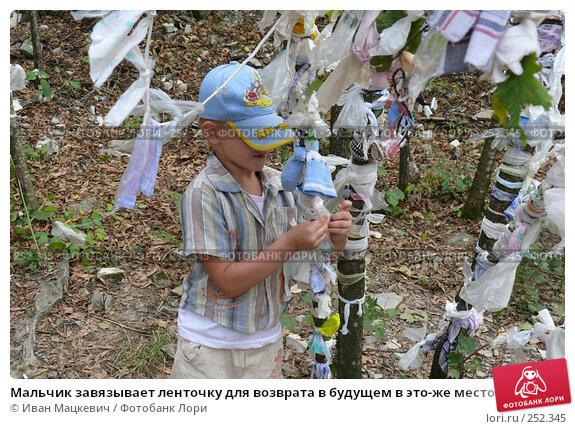 Мальчик завязывает ленточку для возврата в будущем в это-же место, фото № 252345, снято 23 сентября 2007 г. (c) Иван Мацкевич / Фотобанк Лори